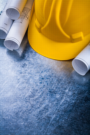 steel background: Rolled up construction plans and safety hard hat on metallic background building and architecture concept.