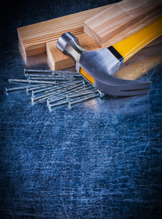 metalware: Copy space image of construction nails hammer and wooden bricks on scratched metallic surface maintenance concept.