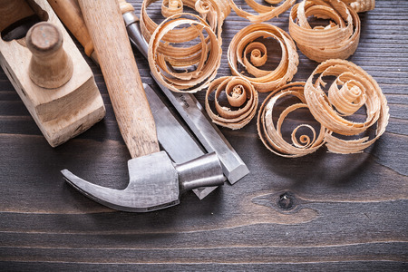 wood planer: Close up image of planer claw hammer metal chisels and wooden curled shavings on vintage wood board construction concept. Stock Photo