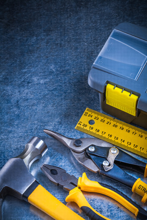 snips: Scratched vintage metallic background with toolbox claw hammer ruler pliers and tin snips construction concept. Stock Photo