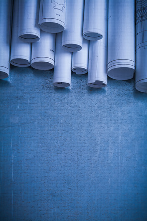 building blueprint: Rolled up white architectural blueprints on scratched metallic surface construction concept.