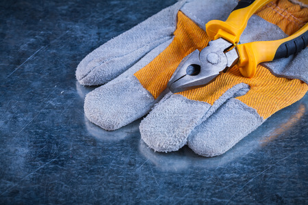 toolset: Protective gloves with pliers on scratched metallic background construction concept.