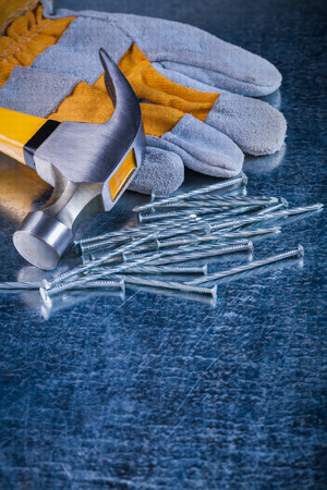 metalware: Safety glove collection of metal nails and claw hammer on scratched metallic surface construction concept.