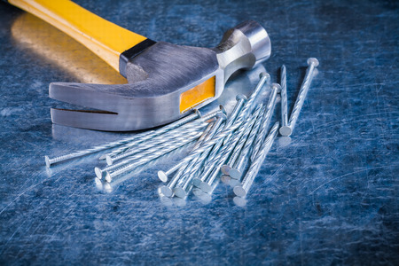 metalware: Variation of construction nails with claw hammer on scratched metallic background maintenance concept. Stock Photo