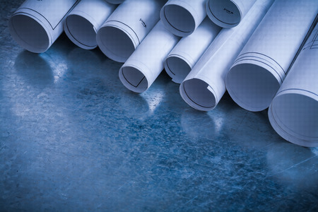 Rolls of white construction plans on scratched metallic background building and architecture concept. Stock Photo