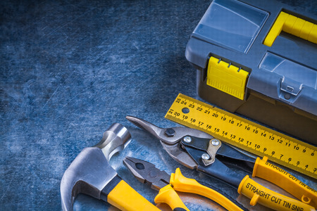 toolbox: Scratched metallic background with toolbox hammer ruler pliers and tin snips construction concept.