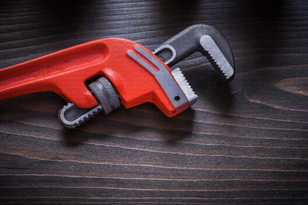 Repairing adjustable wrench on flat brown vintage board construction concept.