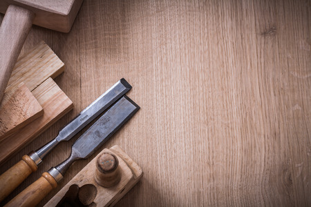 stud: Copy space image of lump hammer planer metal firmer chisels and wooden stud on wood board construction concept.