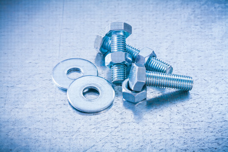 threaded: Metal threaded screwbolts nuts and bolt washers on metallic background construction concept. Stock Photo