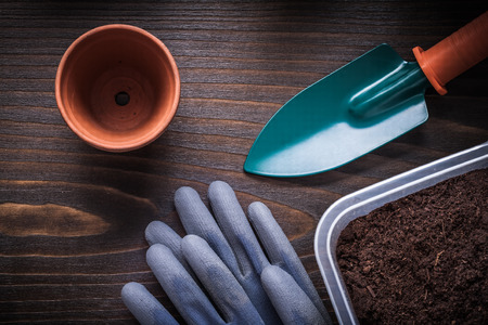 Hand spade working gloves gardening tray with soil and clay pot on vintage wood board agriculture concept.