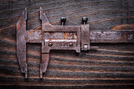 grabado antiguo: Rusted antigua pinza deslizante de medición en la construcción de la vendimia concepto tabla de madera.