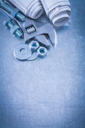 tuercas y tornillos: Arandelas de los pernos llave inglesa ajustable pernos tuercas y enrollados planos de construcci�n met�lica en concepto de mantenimiento de fondo. Foto de archivo