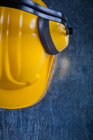 ear muffs: Protective working helmet with safety ear muffs on scratched metallic background construction concept.
