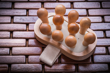 massager: Wood massager with elastic band on textured wooden matting close up view healthcare concept.