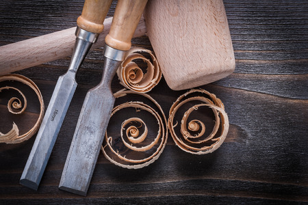 curled up: Set of wooden hammer firmer chisels and curled up shavings on vintage wood board construction concept.