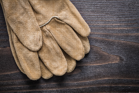 working gloves: Pair of leather working gloves on vintage wooden board construction concept.