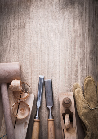 curled up: Wooden bricks hammer curled up scobs planer firmer chisels leather gloves on wood background construction concept.