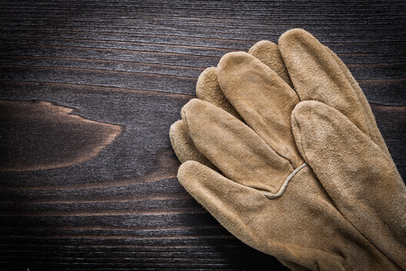 working gloves: Leather working gloves on vintage wooden board copy space image construction concept. Stock Photo