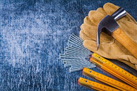 metro medir: Copiar imagen del espacio de trabajo de cuero guantes de uñas metros de medición de madera y garra martillo en arañado la construcción del concepto del fondo metálico. Foto de archivo