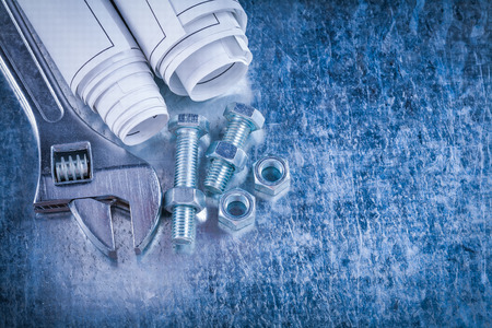 adjustable spanner: Steel adjustable spanner construction nuts bolts and rolls of blueprints on scratched metallic background maintenance concept. Stock Photo