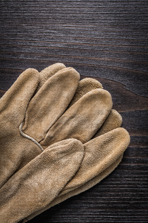 working gloves: Leather working gloves on vintage wooden board vertical version construction concept.