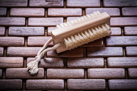 a bathing place: Wood peeling brush on textured wooden matting close up view healthcare concept.