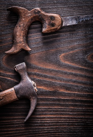 handsaw: Rusty antique handsaw with claw hammer on vintage dark wooden background construction concept.