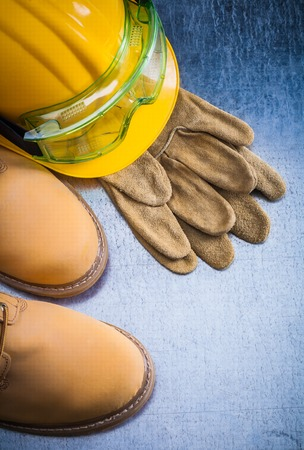 Pair of brown safety lace shoes leather gloves hard hat and working goggles on scratched metallic background construction concept.