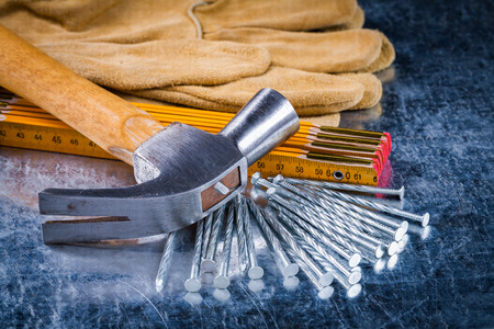 metro medir: Conjunto de guantes de cuero de la construcción uñas metros de medición de madera y garra martillo en arañado metálico concepto del edificio de fondo.
