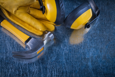 Earmuffs: Noise insulation earmuffs claw hammer and leather protective gloves on metallic background construction concept. Stock Photo