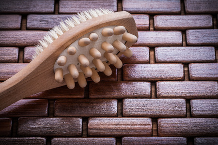 matting: Wood massager and peeling brush on textured wooden matting close up view healthcare concept.