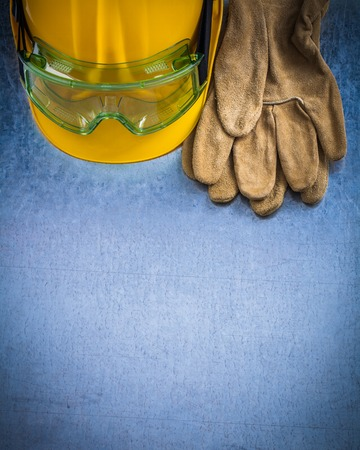 protective goggles: Pair of safety leather gloves building helmet and protective goggles on scratched metallic background construction concept.