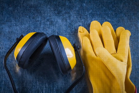 Earmuffs: Protective yellow earmuffs and leather gloves on scratched metallic surface construction concept.