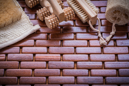 wisp: Wisp of bast loofah wood peeling brush and massager on textured wooden place mat sauna concept. Stock Photo
