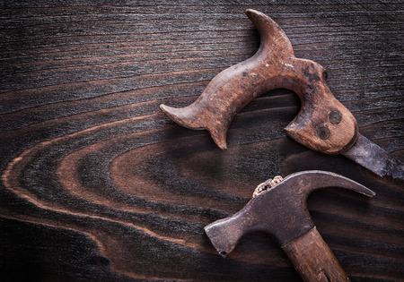 serrucho: Sierra de mano de metal oxidado con la garra martillo en la vendimia tabla de madera oscura de cerca concepto vista de la construcci�n. Foto de archivo