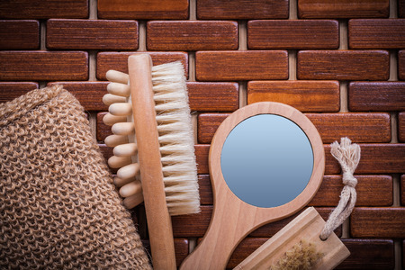 massager: Wood massager looking-glass body scrubber and peeling brush on textured wooden mat sauna concept.
