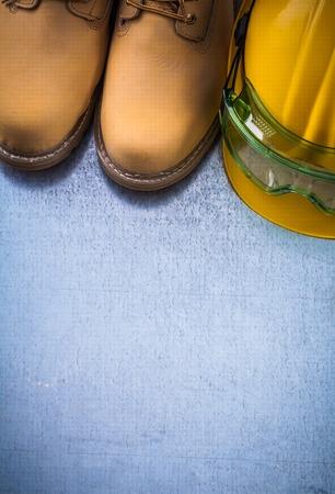 calzado de seguridad: Par de zapatos de seguridad que construyen el casco y las gafas de plástico transparentes sobre arañado la construcción del concepto del fondo metálico. Foto de archivo