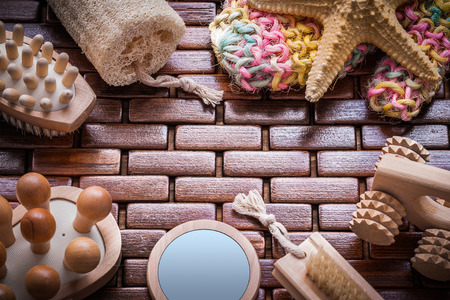 bath sponge: Loofah handglass massagers peeling brushes starfish and colorful bath sponge on textured wooden table mat sauna concept.