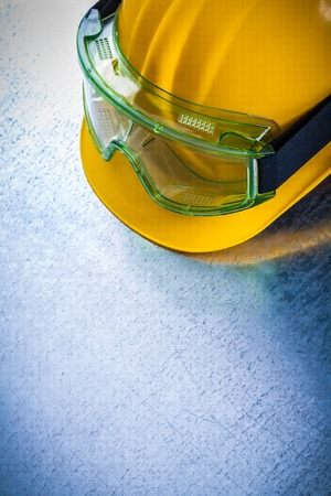 yellow hard hat: Top view of yellow hard hat with transparent protective glasses on scratched metallic background construction concept. Stock Photo