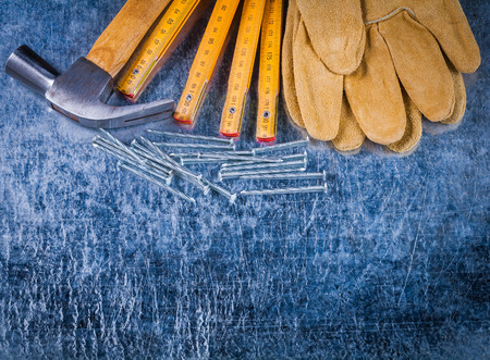 metro medir: Grupo de protección Guantes de trabajo uñas metros de medición de madera y garra martillo en arañado la construcción del concepto del fondo metálico.