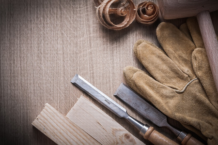 chisels: Wooden building boards mallet curled up shavings firmer chisels leather gloves on wood background construction concept.