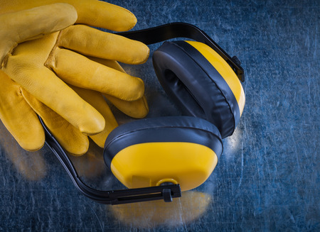 ear muffs: Safety yellow ear muffs and pair of leather construction gloves on scratched metallic surface building concept.