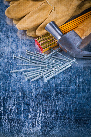 metro medir: De cuero guantes de construcción uñas metros de medición de madera y garra martillo en fondo metálico rayado concepto de construcción versión vertical. Foto de archivo