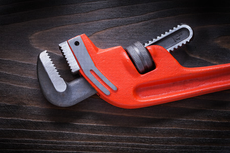 pipe wrench: New red pipe wrench on flat brown vintage wooden board construction concept. Stock Photo