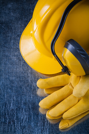 ear muffs: Hard hat safety ear muffs and leather protective gloves on scratched metallic surface construction concept.