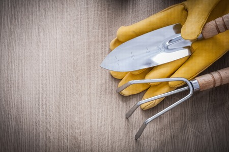 gardening gloves: Metal hand spade rake yellow leather gardening gloves on wooden board agriculture concept. Stock Photo
