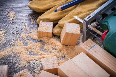 scobs: Pencil electric jigsaw sawdust working protective gloves and wooden planks on vintage wood background construction concept.