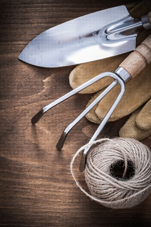 gardening gloves: Metal hand spade rake pair of brown leather gardening gloves and hank of rope on vintage wooden board agriculture concept. Stock Photo