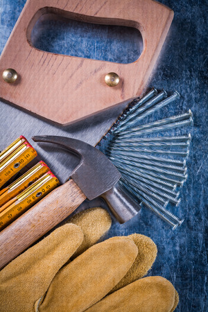 construction nails: Hand saw protective gloves construction nails wooden meter and claw hammer on scratched metallic background close up view building concept.
