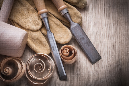 curled up: Wooden mallet curled up planning chips firmer chisels leather gloves on wood board construction concept. Stock Photo